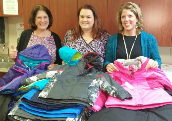 Jill Lacaillade (center) with group members and coats purchased from donations.